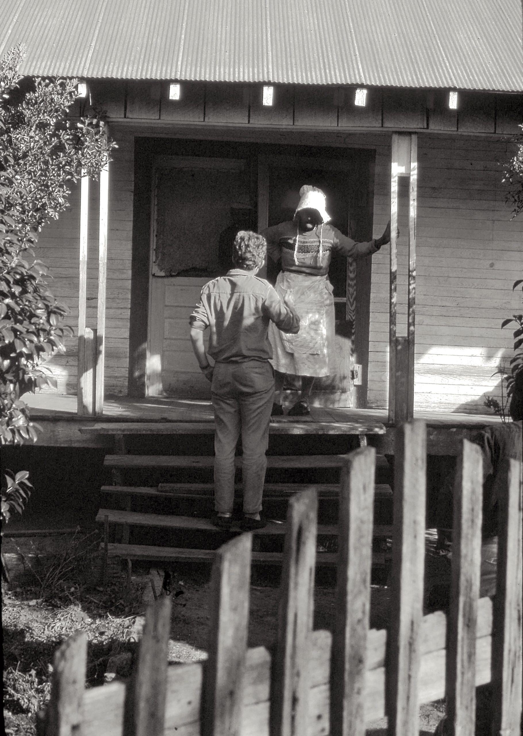 A member of Jim Lemkin's group meets an African-American woman on her front step to discuss the Voting Rights Act of 1965 and the lifting of voter suppression tactics.
